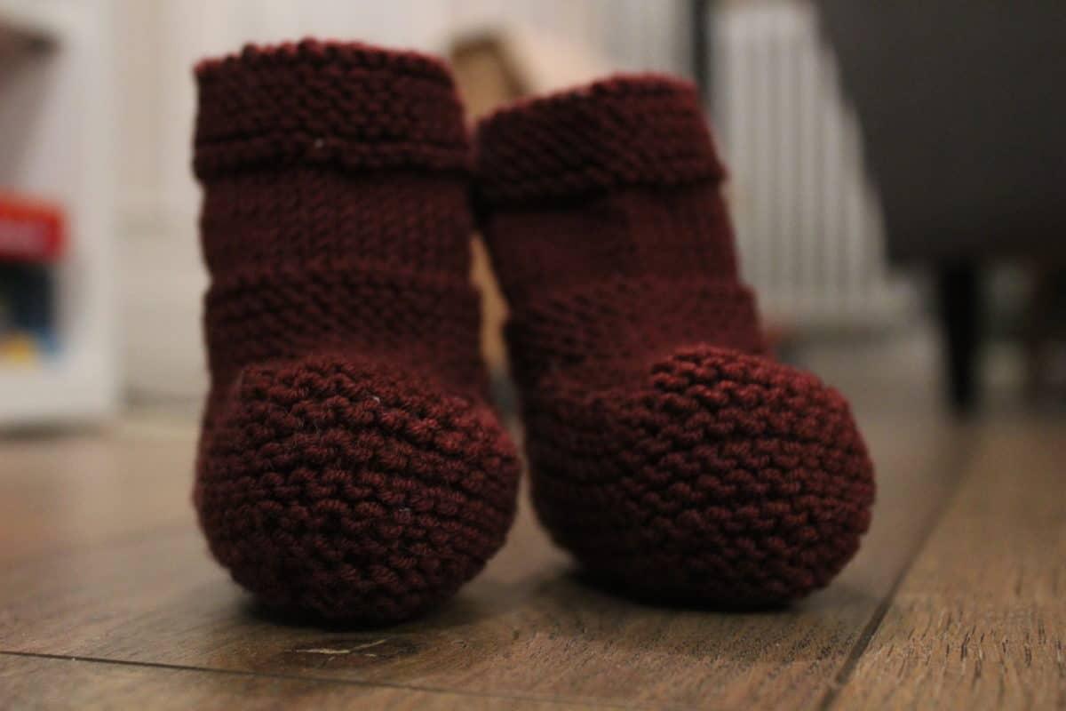 une paire de chaussons de bébé tricotés bordeaux biboudou